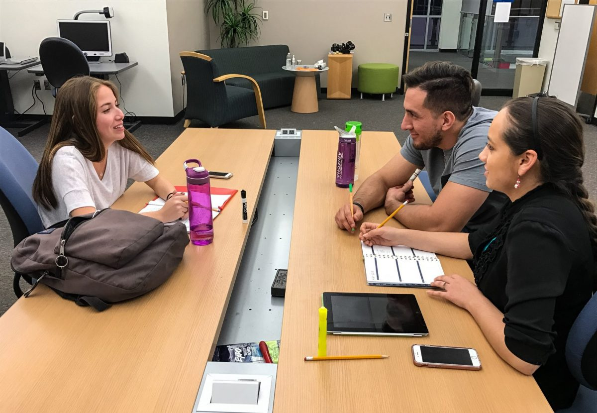 PHOTO: a study session, three people sit across a table from each other with study supplies in front of them. They smile at each other as they work on their books.