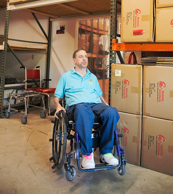 PHOTO: a mature man in blue polo shirt and jeans sits in a wheelchair in a warehouse setting. There are boxes on his left and a red Goes Anywhere, Commode, Shower, and Tub Chair behind him.