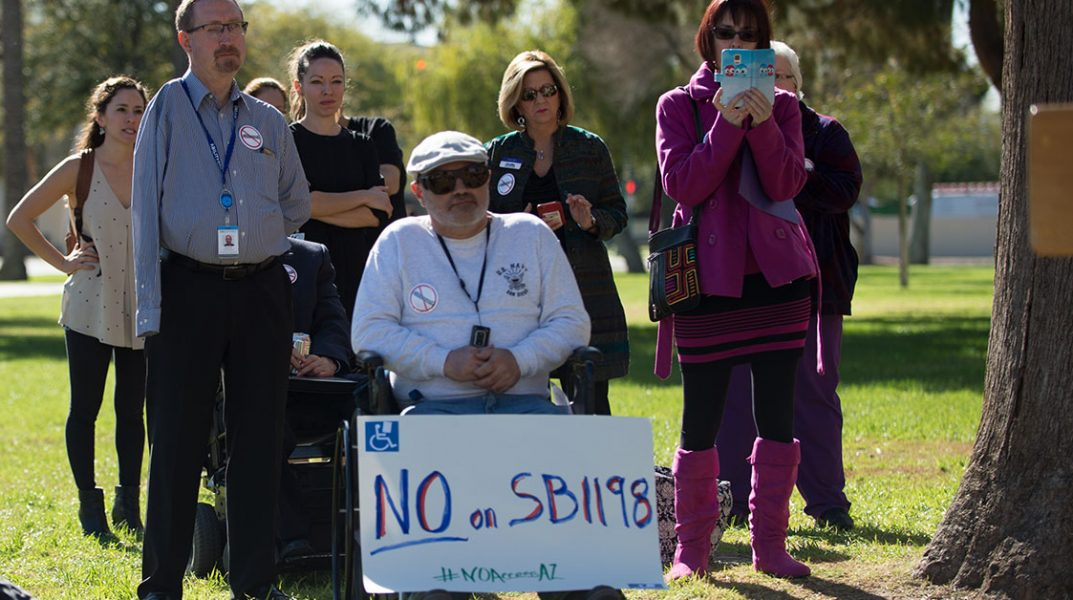 "Disability advocates rally at state Capitol. image shows man in wheelchair with sign reading "" No on SB119."