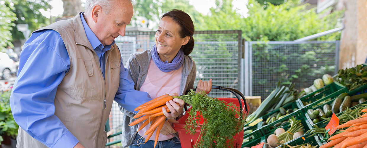 Caregiver assisting a man by carrying a basket of vegetables in the market.