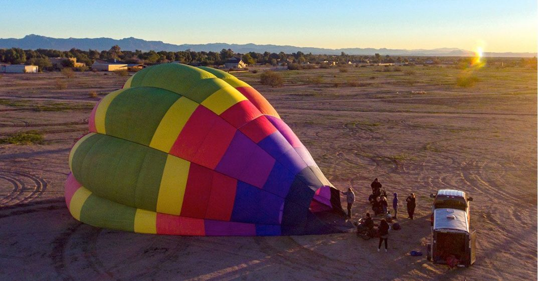A small crowd assembles next to a large, colorful hot air balloon in an open field