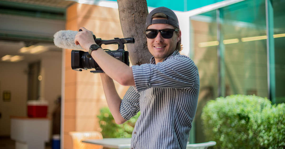 Photographer Clinton McDaniel poses with his camera in the Ability360 courtyard area.