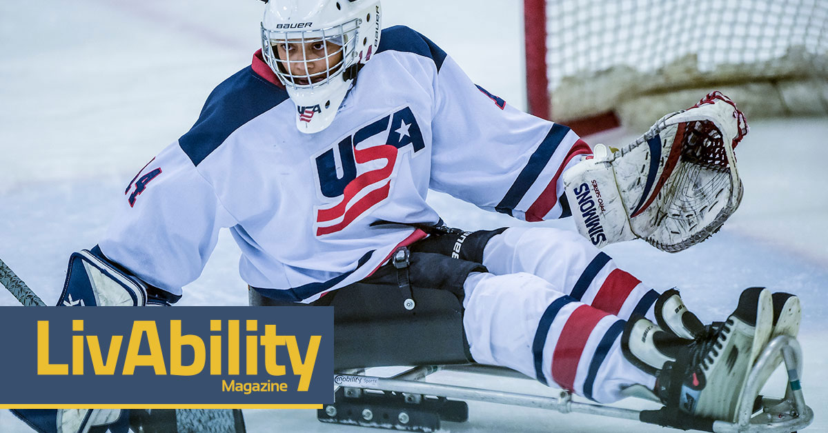 Gabby Grave-Wake guards a hockey net on an ice rink in her Team USA uniform.