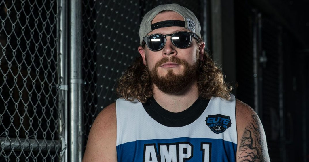 Nick Pryor sits on a stool. His prostetic leg propped up on the wrung. He wears a blue AMP1 jersey. His number is forty-four and a half. He holds a basketball under his arm. He wears sunglasses and his baseball cap turned backward.