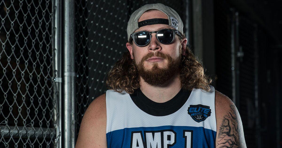 Nick Pryor sits on a stool. He wears a blue AMP1 jersey. He wears sunglasses and his baseball cap turned backward.