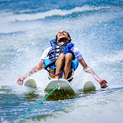A man sits on an adapted water ski with his head back and his arms out in what appears to be great relaxation or reverence