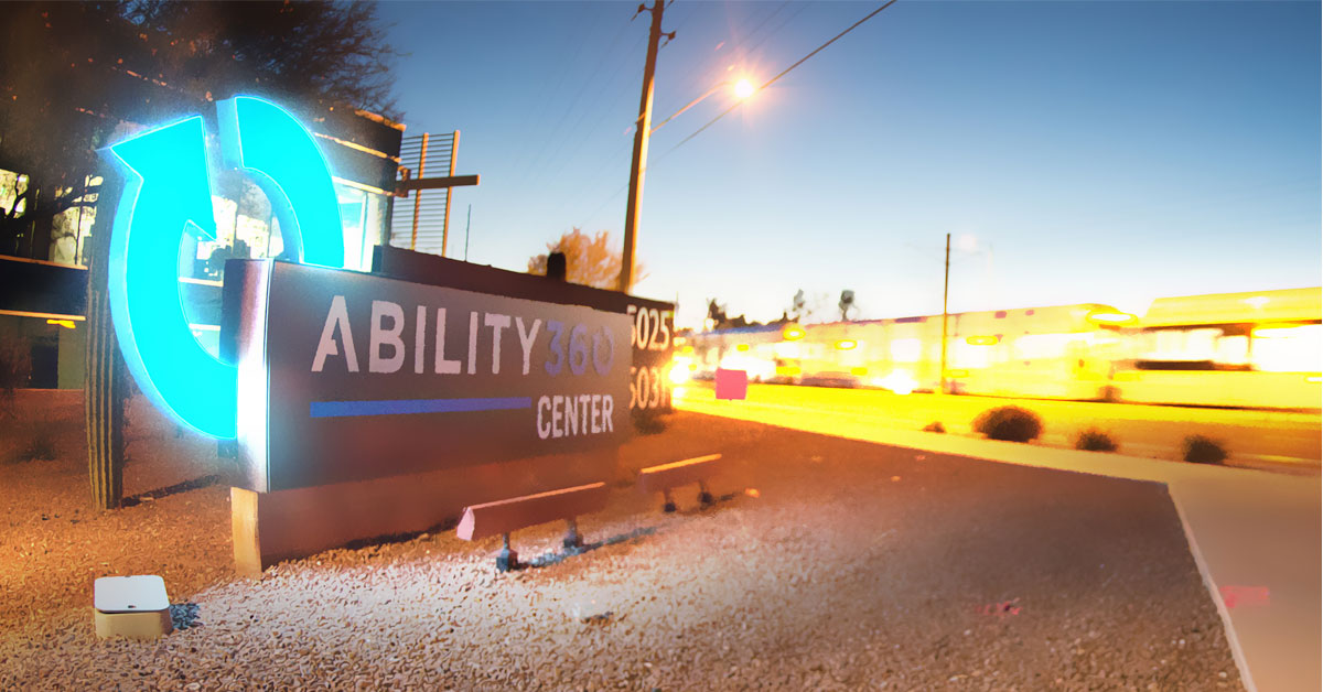 The Ability360 center's sign is lit up after the sun sets. The light rail goes by in the background.
