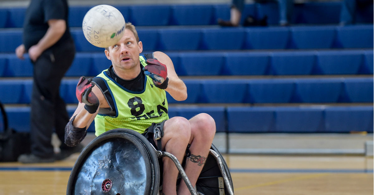 Wheelchair rugby coach Scott Hogsett prepares to catch a ball