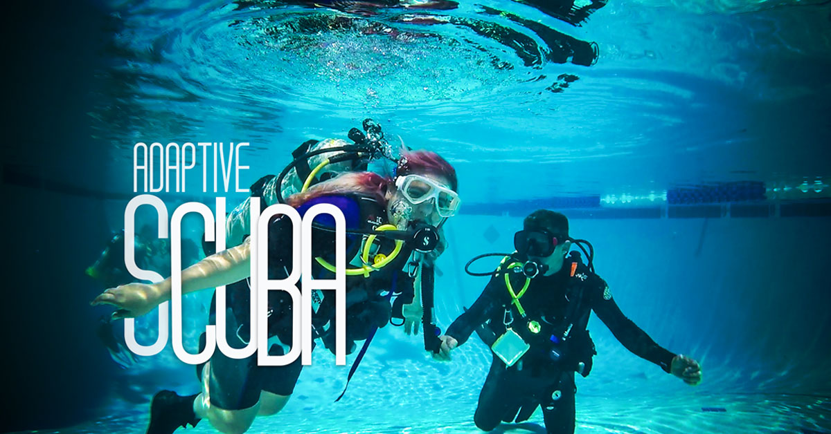A SCUBA diver and her instructor pose underwater for the camera.