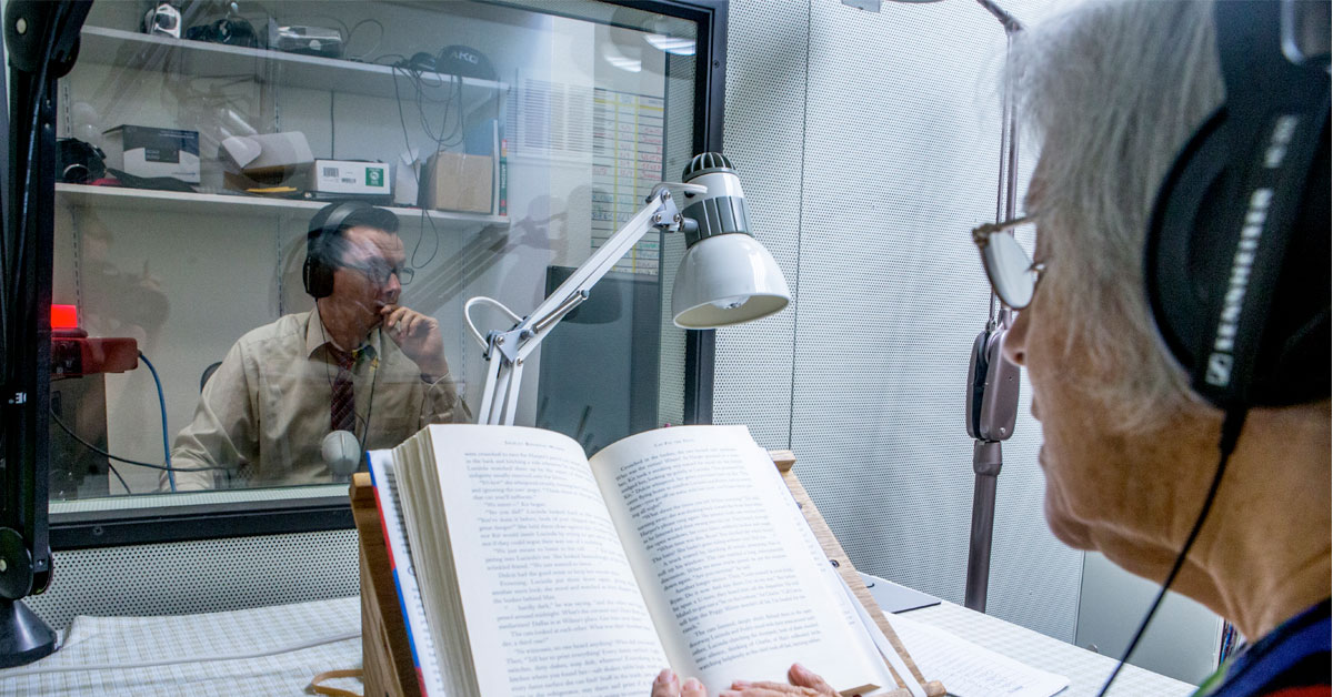 A Talking Books Library employee narrates a book in a recording studio
