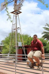 CJ Horton sits on a fence by a windmill.