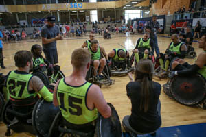Scott Hogsett sits with his team, all sporting neon green jerseys.