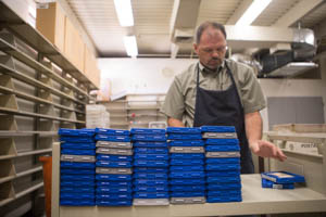 A Talking Books Library employee stacks plastic audiobooks.
