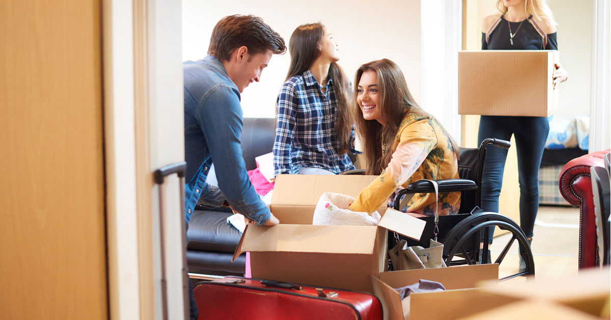 Four young people, three women and one man, one in a wheelchair. They are unpacking boxes, clearly settling into an apartment.