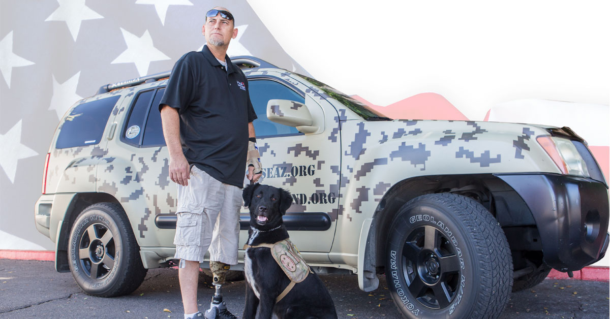Photo, Soldier's Best Friend, shows a SUV with camouflaged paint. A large Labrador sits at attention wearing a camouflage service dog vest. Beside him stands a man with sunglasses on his forehead, a blue golf shirt, brace on his left arm, cargo pants, gym shoes. His left leg is amputated below the knee. Prosthetic device shows in the photo.