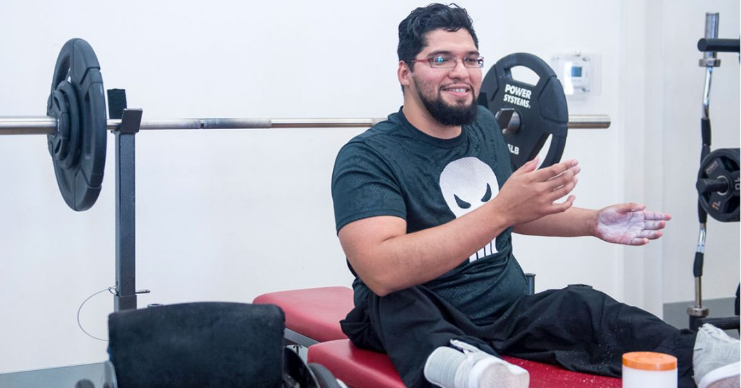Photo shows mat table with a young man sitting on it wearing white gym shoes, a blue T-shirt with a skull, and black pants. His wheelchair sits beside the mat table. A barbell with a lot of weight is evident in the background.