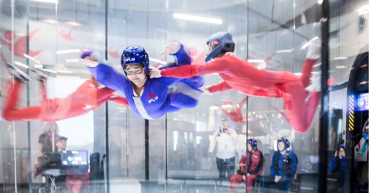 Photo, a large glass enclosure. The figures are blurred, as they are clearly in motion. A young person in a blue jumpsuit, goggles, and helmet is suspended off of the ground, belly down, arched as a parachutist would be, supported on each side by people wearing red jumpsuits and helmets. In the background, others wearing jumpsuits and helmets wait their turn