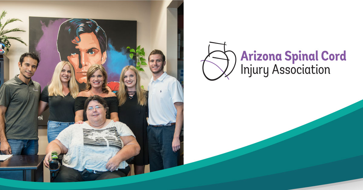 Photo shows the Arizona Spinal Cord Injury Association staff. In the background a large painted portrait of Christopher Reeve as Superman. In the front is Karen Halgren. She sits in her power wheelchair. Behind her, Guillermo Zeldon, Andrea Miller, Shannon Carter, Allison Miller, Cameron Harris.