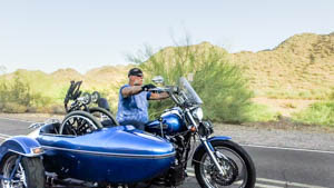 Billy Marvin is on his motorcycle, his wheelchair folded in the sidecar. He wears a black Harley do-rag, black leather gloves, sunglasses, and a blue T-shirt.
