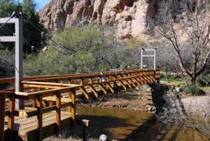 A wooden suspension bride reaches over a creek