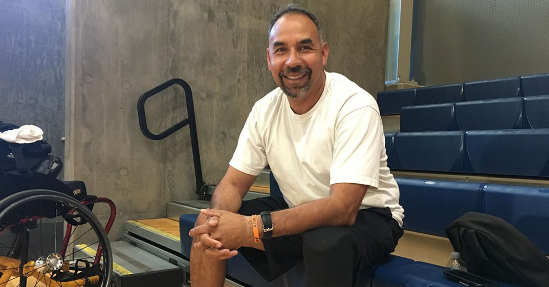 Alcaraz smiles with his hands folded on his lap, he is sat on a bleacher seat (indoors)