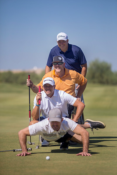 photo shows four men in a humorous position. In the foreground, the young man looks poised to break dance, the one behind him crouches, the one behind him sits in a wheelchair, and the one behind him stands up. They all stare intently at a golf ball in a comic position.