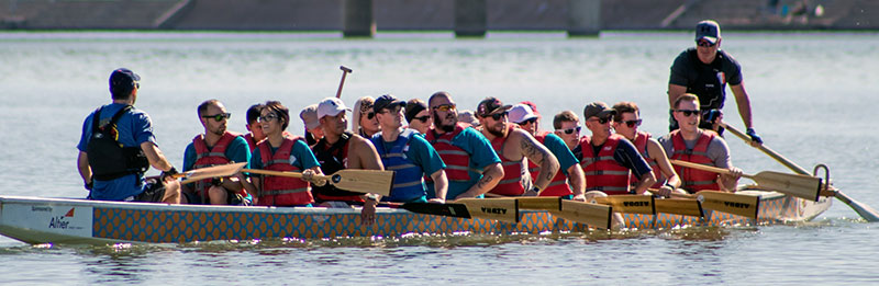 . Photo shows several people rowing a dragon boat. In the front is a coach calling the stroke. Behind, a man stands and operates the rudder.