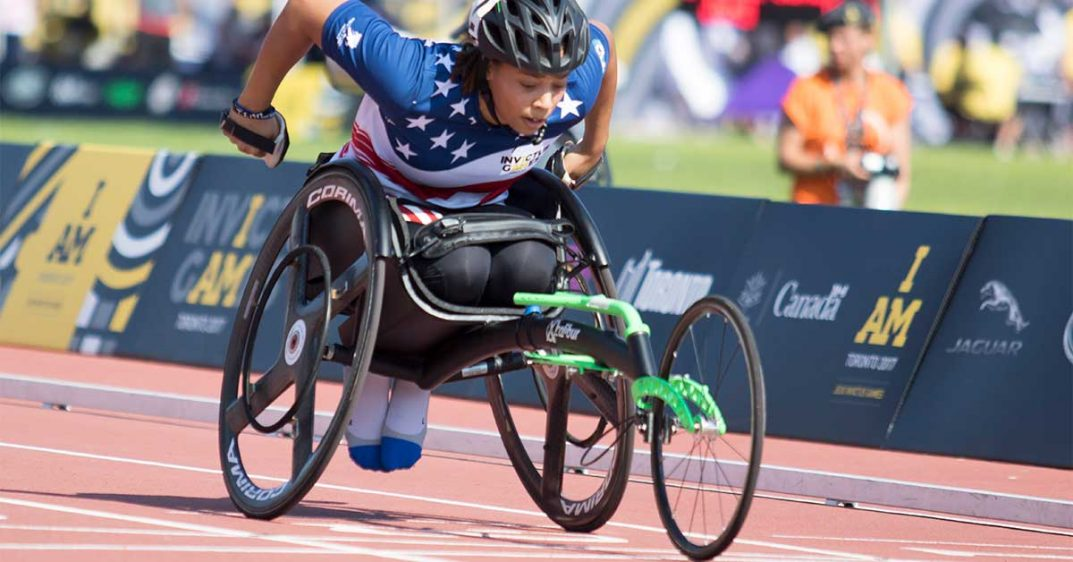 "young woman in racing wheelchair dressed in red, white, and blue track and field uniform with the insignia ""Invictus Games"" on the chest. She is in deep concentration, her muscles bunched as she rolls forward."