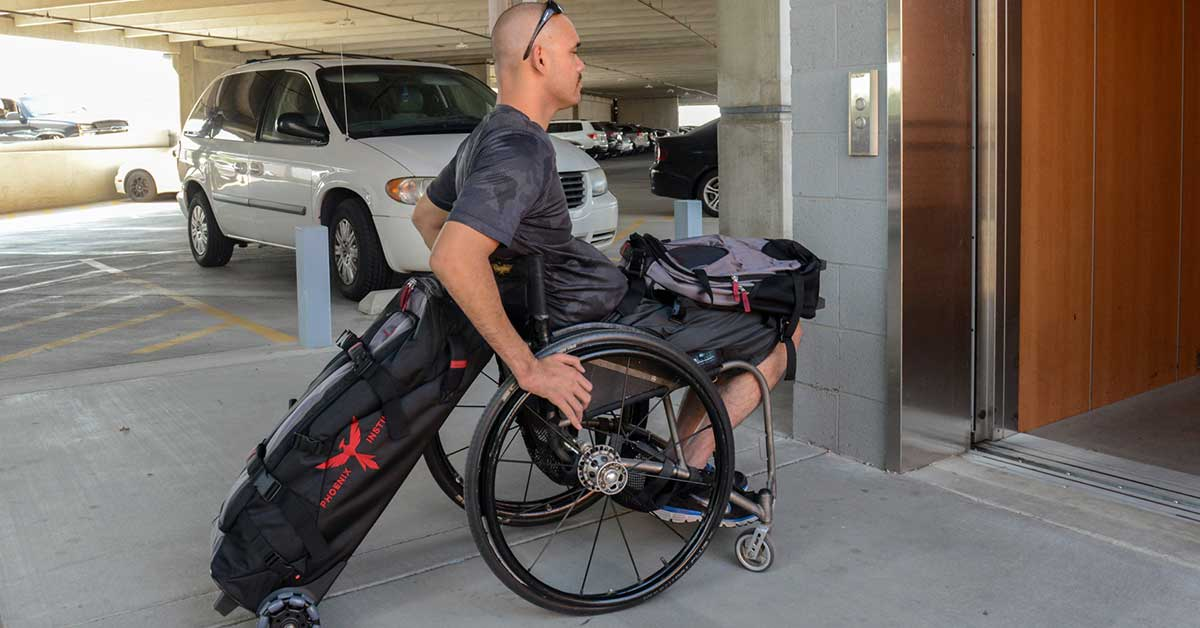 Photo shows a young man with close-shaved hair and sunglasses. Uses a manual wheelchair and the Unstoppable gear bag is attached to the back of his wheelchair. He has another messenger bag on his lap as he enters an elevator in a parking garage.