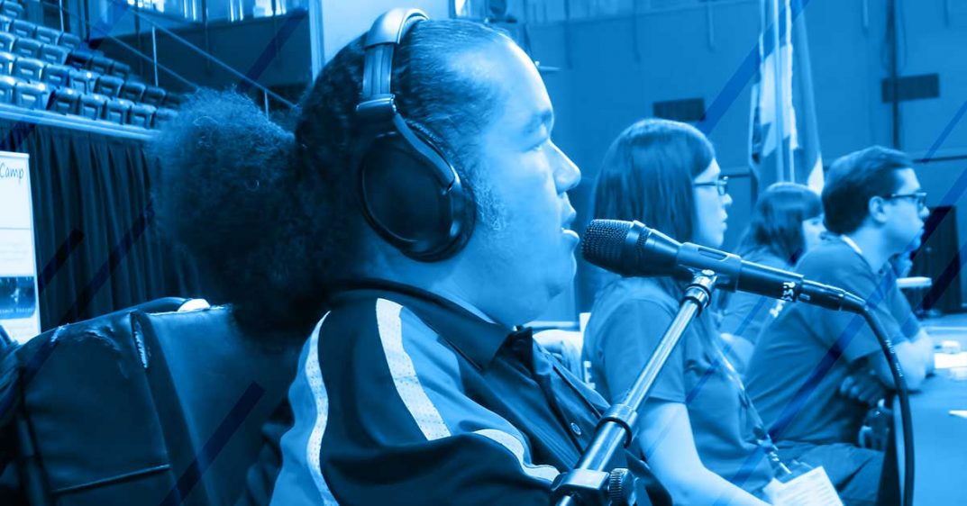 shows a photo of Tony Jackson. He sits in a power wheelchair, speaking into a microphone, wearing large professional headset. Several other people sit beside him. He is narrating a sporting event. The photo is stylized with a dark blue wash.
