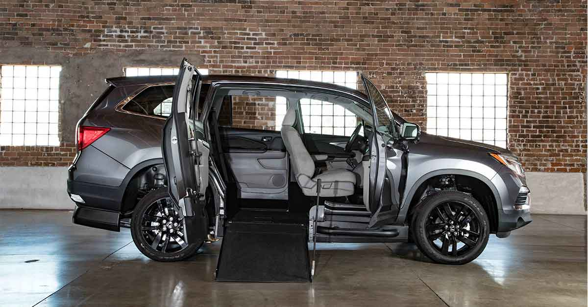 VMI's new accessible Honda Pilot. It is a gray SUV shown from the passenger side. The passenger door and rear doors are open, showing a ramp and an open rear compartment to hold a wheelchair.