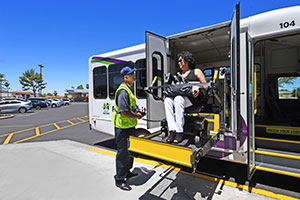 . Photo shows white van, wheelchair-accessible, ramp comes out the passenger side rear compartment. A woman in a power wheelchair is going down the ramp and a worker wearing a yellow vest and hat stands beside guiding. Logo on the side of the van is Valley Metro Paratransit.