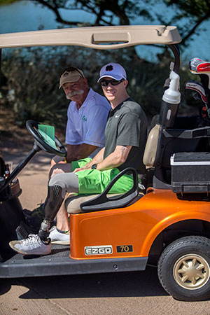Photo shows an orange golf cart. Man in foreground is a young man with baseball cap and sunglasses and an above-the-knee prosthetic device. Sitting beside him, an older man with a silver mustache, sunglasses, and baseball cap, and a golf scorecard.