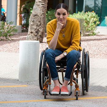 Gina Schuh smiles at the camera. She is a wheelchair user sitting in a manual wheelchair, wearing a gold sweater, blue jeans, and pink shoes.