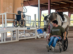 Photo shows Draper in a wheelchair, pink lead across her lap, leading the large gray horse known as Barbara. A wheelchair hangs on a lift in the background near a raised ramp to allow people to mount that horse.