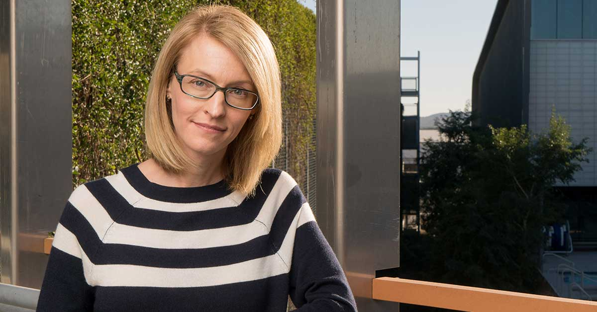 April Reed smiles at the camera as a portrait. A young blonde woman with glasses and blue eyes, very serene smile, stands with her hands crossed, and she's wearing a black and white striped sweater.