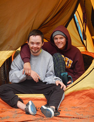 A young woman has her arm around a young man. They are sitting in the doorway of a tent and looking out, smiling at the camera.