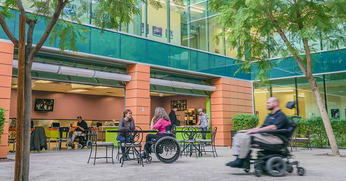 Photo of the new Café Cultivate. Large garage doors are open. It is the Ability 360 courtyard. In the right corner, a man in motion in a wheelchair. Sitting at the tables in the center are two women. Behind them stand two men at the café counter and inside, another man sits drinking coffee.