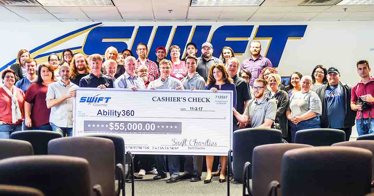 photo of a giant check with the Swift Charities logo on it. It is made payable to Ability 360. It's a cashier's check dated 11/3/17 in the amount of $55,000. It's a giant check being held by eight people, with probably another 20 people behind them with the Swift logo evident in the background.