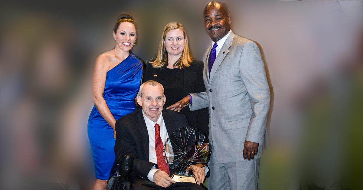 Photo shows Phil Pangrazio sits in his wheelchair and holds a large award. He is surrounded by a woman in a blue gown, a woman in a black suit, and a man in a gray suit.