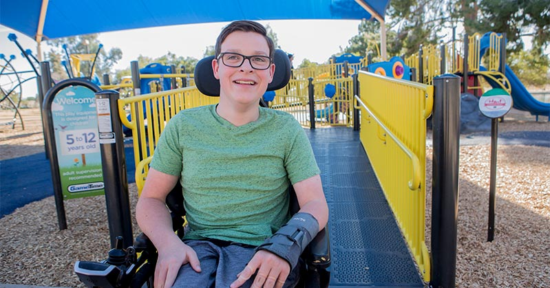 Aidan Ringo sits at the new playground equipment which is in all primary colors. He smiles from his wheelchair.