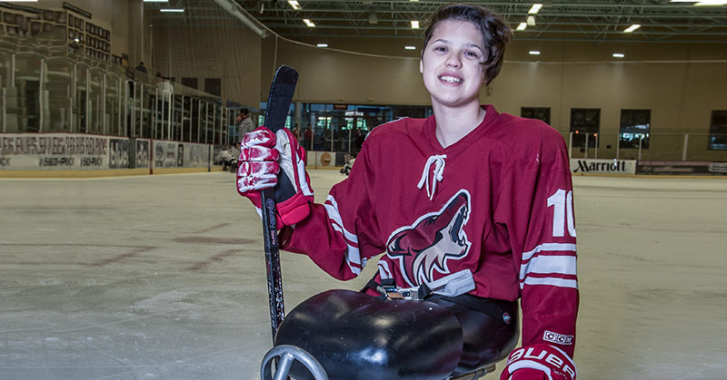 Portrait of Lera Doederlein. She is on her hockey sled on the ice rink. She has her stick in her hand. She wears her Coyotes uniform.