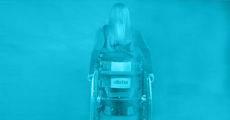 A woman in a wheelchair faces away from us. She has long hair, her hand on the push rim, the hashtag me too visible on the back of her chair. She is lit in teal.