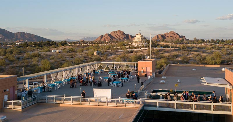 Panoramic view of the Ability360 roof with gala tables parked in front and a view of the Tovrea Castle.