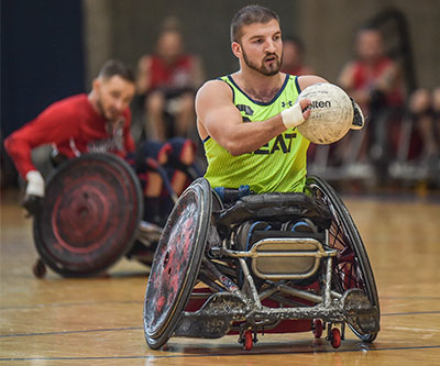 A man playing wheelchair rugby. He has the ball. There are other players behind him.