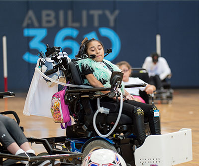 A young girl playing power soccer. She is about to hit the ball with her power chair.