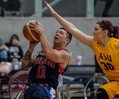 A man and a woman playing wheelchair basketball. He is about to make a shot with the basketball and she is trying to block it.