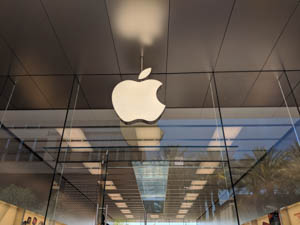 Photo shows the Apple logo against silver walls and florescent lights leading down a hallway.
