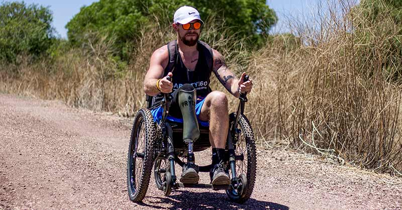 photo of a deep blue sky and trees in the background, tall brown grasses, and a dark gravel path. In the foreground is a man in a wheelchair with large knobby tires and levers that he seems to be pumping to propel himself. He wears a white hat, sunglasses, black tank top with the Ability360 logo prevalent. His prosthetic leg prevalent in the foreground.