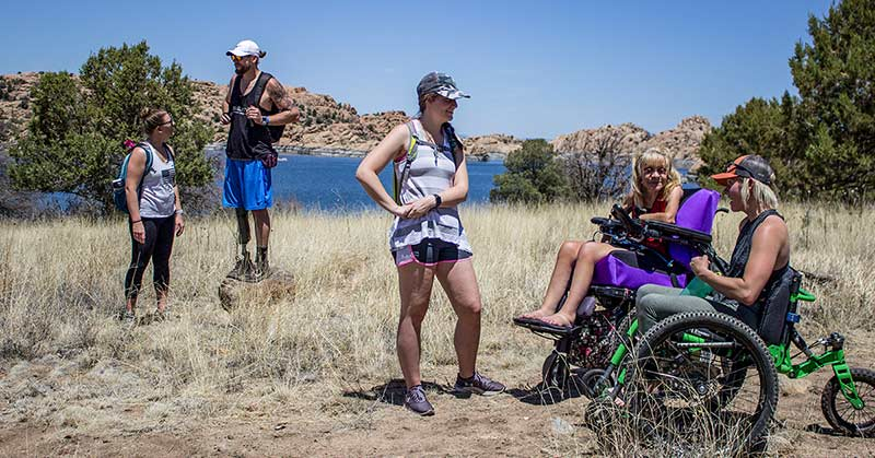Photo shows tan bluffs in the background under a deep sky and a lake in the midground, and in foreground, in a brown grassy area with a path, shows a number of people. Two women stand and interact with other folks. A man with a prosthetic leg carrying a backpack stands on a rock, and in the foreground, two women in wheelchairs, one power wheelchair, one mountain chair, look on.